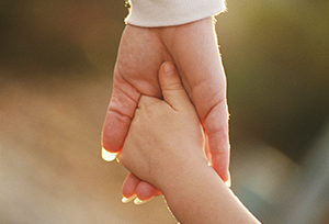 Child holding hands with adult - sunlight on hands only_resized